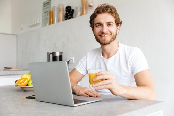 快乐的小胡子男人在家里的桌子上用笔记本电脑