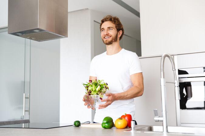 一个英俊的年轻人在厨房的照片在家做饭蔬菜做沙拉