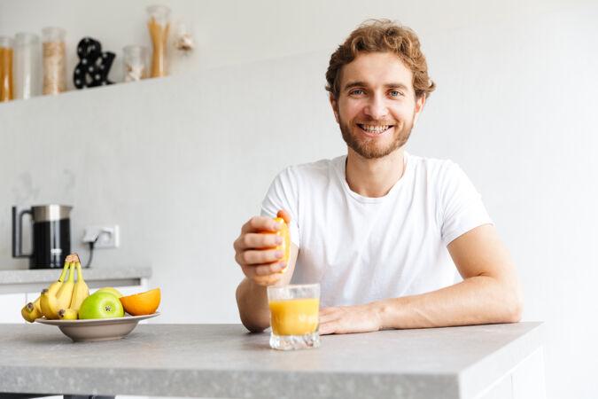 图为一位快乐的留着胡子的年轻人在家里用水果做果汁