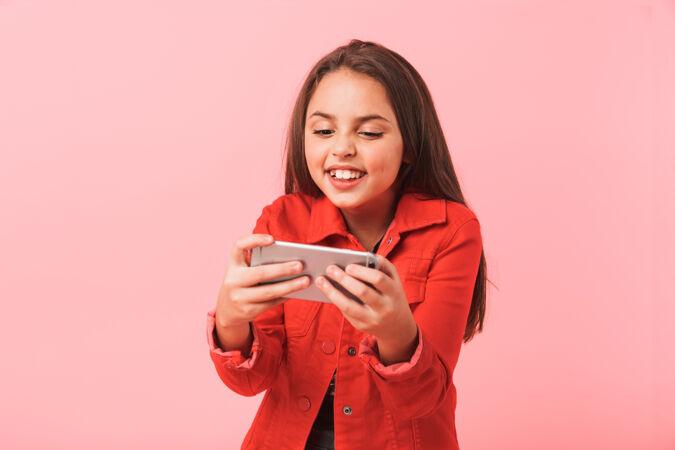 兴奋的少女在手机上玩视频游戏 而站着 隔着红墙孤立的形象