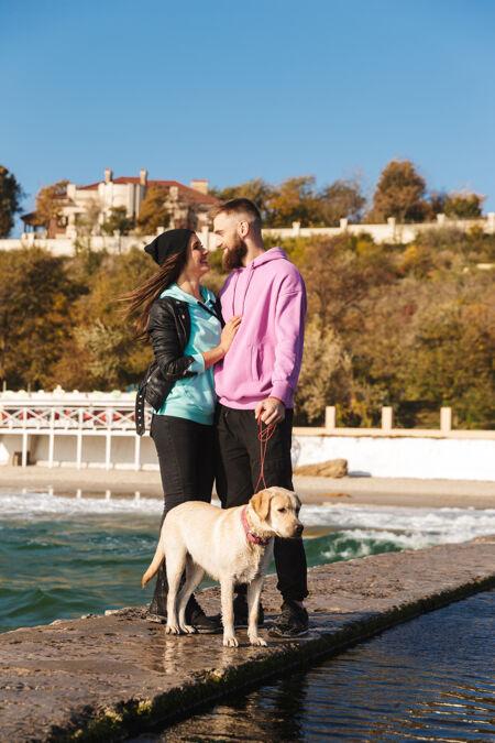 迷人的年轻夫妇带着他们的狗在海滩散步