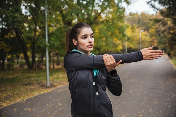 微笑的年轻健身女孩在公园锻炼身体