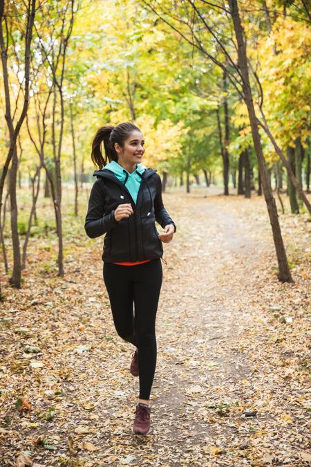 照片惊人的年轻漂亮的健身女跑步者在公园户外跑步
