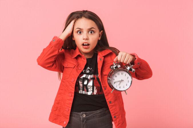 震惊的少女在随意拿着闹钟 而站着 隔着红墙孤立的形象