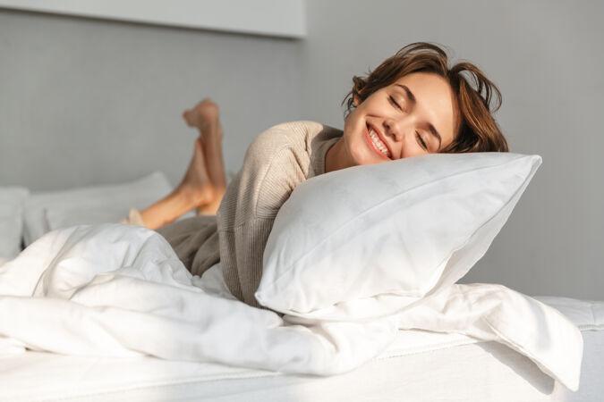 微笑的年轻女孩早上在床上放松
