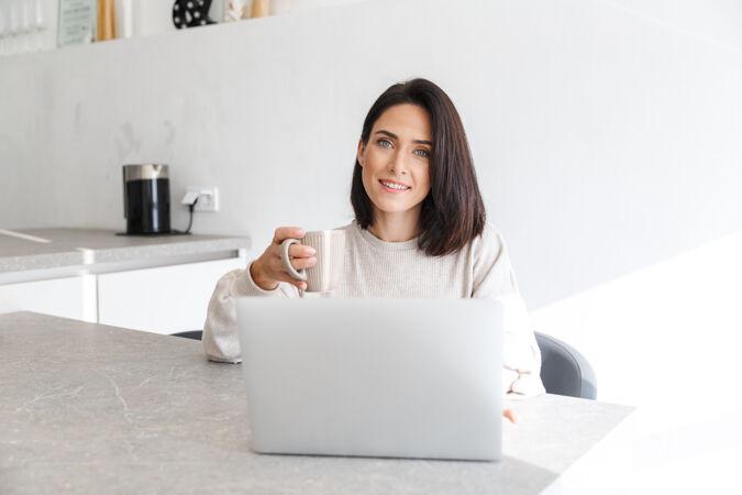30多岁的成年女性坐在明亮的房间里 一边用笔记本电脑 一边坐在白色的墙上