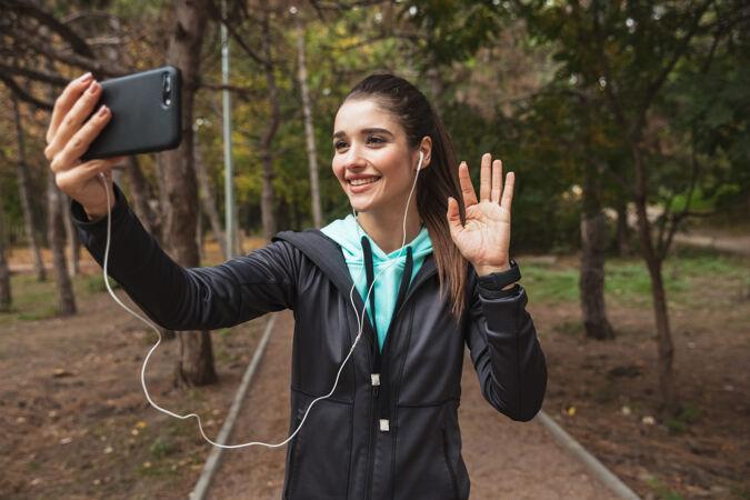 微笑的健身女士戴着耳机听音乐 站在公园里自拍