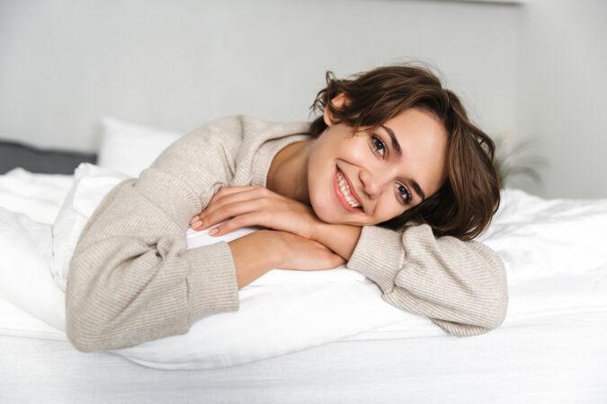 微笑的黑发女人在家躺在床上休息