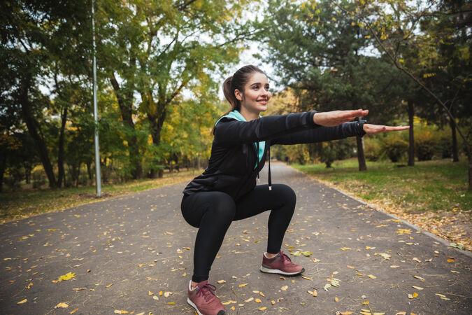 微笑的年轻健身女孩在公园里做运动 蹲着