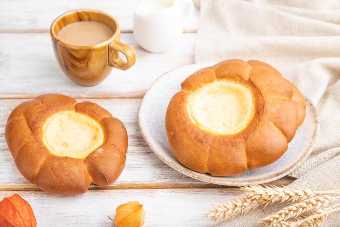 酸奶油面包和一杯咖啡在白色木制背景和亚麻布上纺织面料观看 特写 选择性聚焦