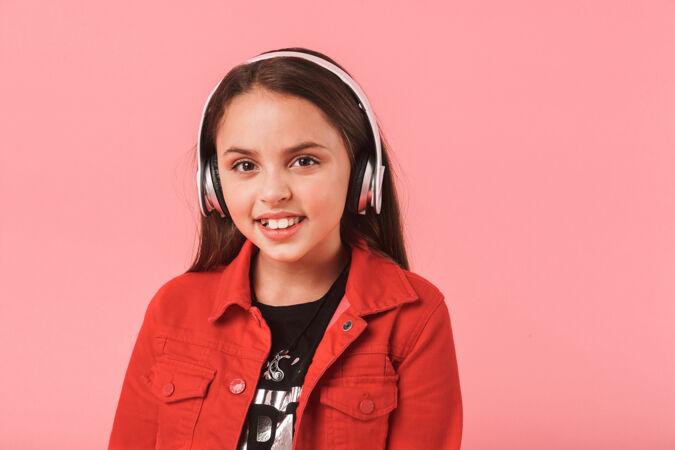画面中快乐的小女孩戴着休闲耳机听音乐 隔着红墙孤立着