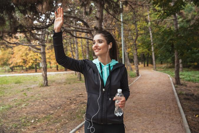 微笑的健身女 戴着耳机听音乐 站在公园里拿着一瓶水