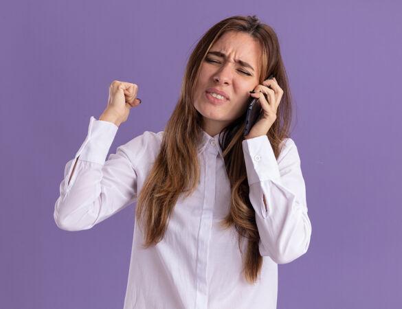 一个年轻漂亮的白人女孩不停地用拳头打电话