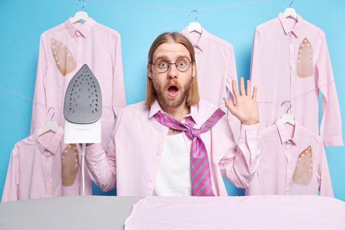 男人穿衣服参加约会或公司会议用电熨斗熨衣服在熨衣板上忙着做家务