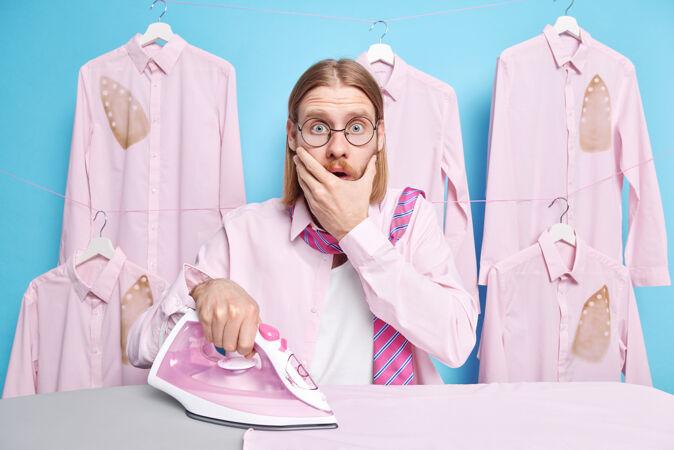 男人张嘴瞪着吓坏了 忘记了妻子又一个任务 在熨衣板附近摆姿势 把衣服染成蓝色