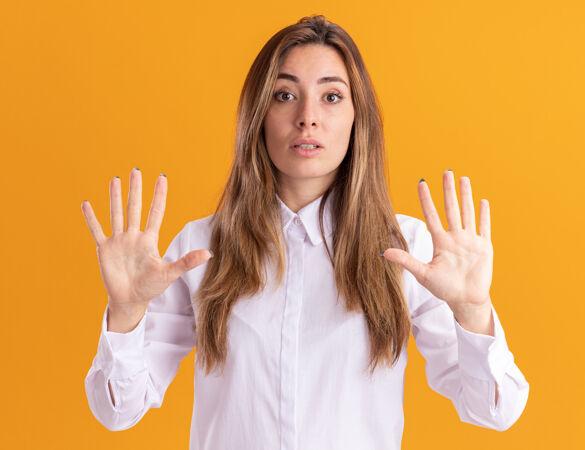 震惊的年轻漂亮白人女孩举手站着