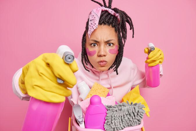 男人留着长发锁 摆着带清洁用品的姿势 戴着橡胶手套 拿着清洁剂喷雾剂或隔离在粉红色上的洗涤剂