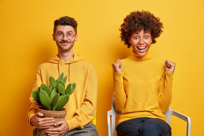一个留着非洲头发的女人握紧拳头 很高兴庆祝成功 她坐在一张舒适的椅子上 靠近被隔离在黄色地板上的男朋友