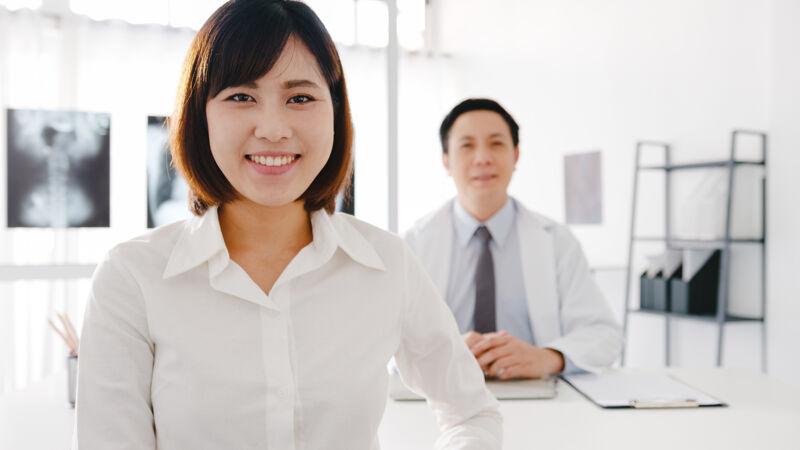 自信的亚洲男医生穿着白色的医疗制服 年轻的女病人看着相机 微笑着在诊所或医院的服务台上接受医疗咨询