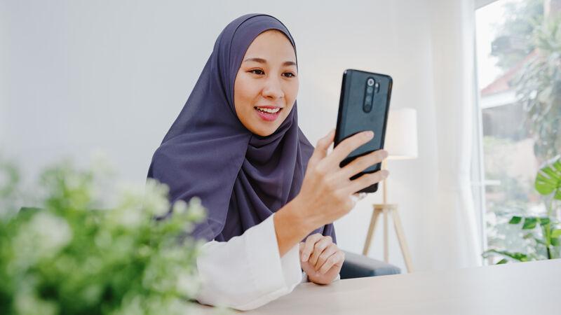 年轻的穆斯林女商人使用智能手机通过视频聊天与朋友交谈头脑风暴在线会议 同时在客厅远程工作