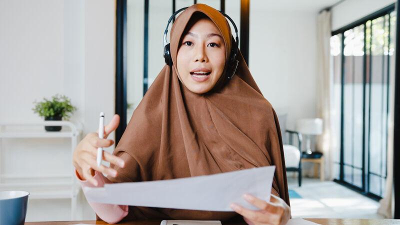 穆斯林女士戴着耳机 用笔记本电脑和同事通过视频电话谈论销售报告 同时在客厅远程工作