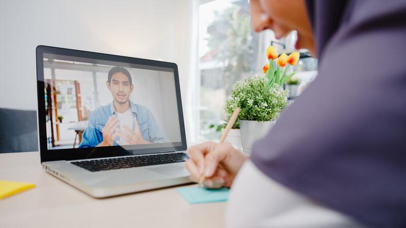 穆斯林女商人使用笔记本电脑通过视频电话与同事讨论计划头脑风暴在线会议 同时在客厅远程工作