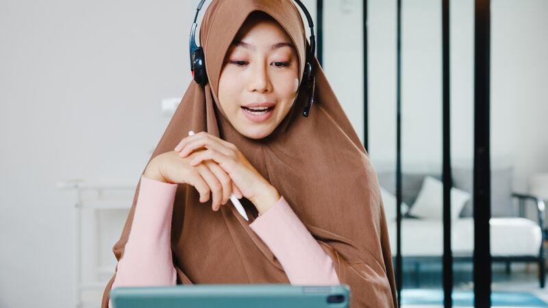 穆斯林女士戴着耳机使用数字平板电脑在家里厨房工作时 通过视频会议与同事谈论销售报告