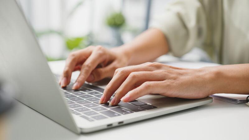 自由职业的年轻女商人休闲装使用笔记本电脑在家客厅工作