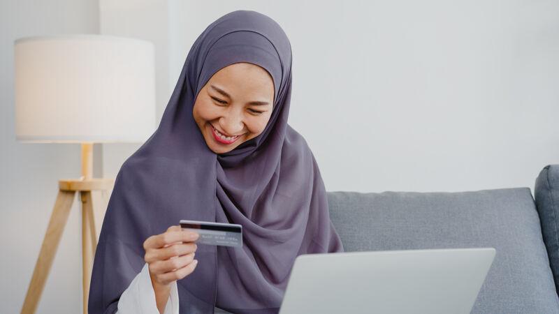 亚洲穆斯林女士使用笔记本电脑 信用卡购买和购买电子商务互联网在客厅的房子