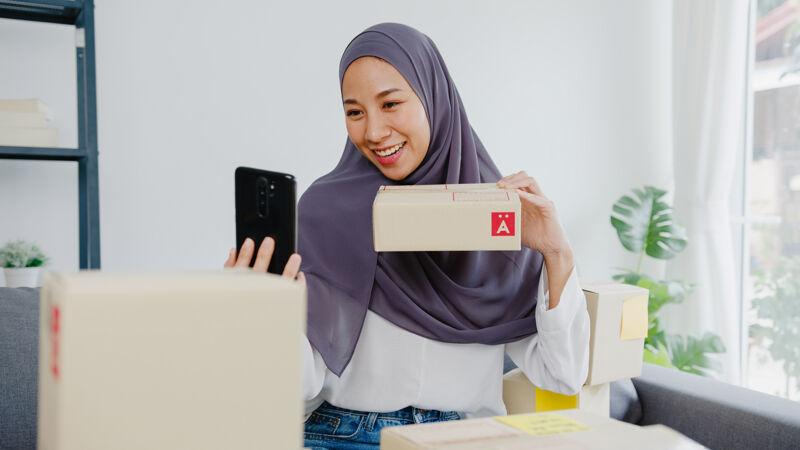 年轻的穆斯林女商人博客使用手机摄像头录制vlog视频直播审查产品在家办公