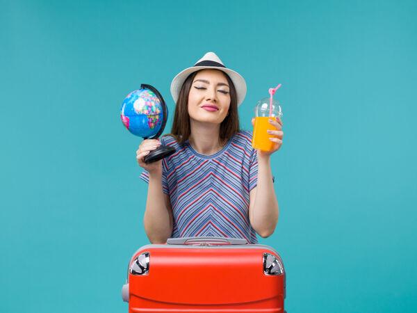 前景度假中的女人拿着果汁和地球仪在蓝色的背景海上航行暑假