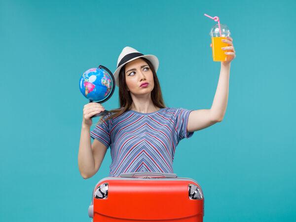 前景度假女人拿着果汁和地球仪在蓝色书桌上海上旅行度假暑假旅行