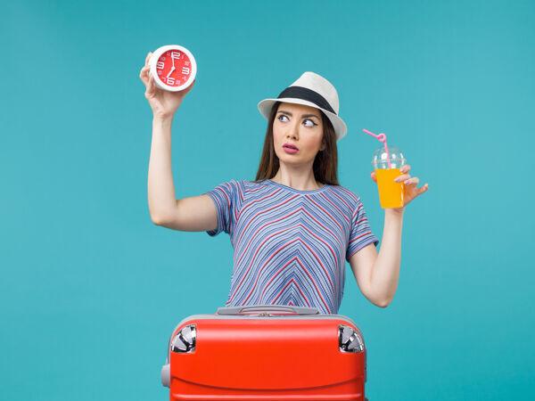 前景:度假中的女人拿着果汁和蓝色桌子上的钟远航度假海上旅行