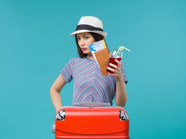 正面图:度假中的女人拿着果汁和蓝色背景的机票在海上避暑飞机上旅行