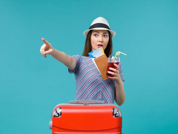 前景度假中的女人拿着果汁和机票上蓝色背景的航程女海上避暑飞机