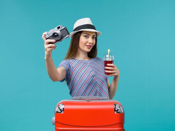 前景度假中的女人拿着果汁带着相机在蓝色的背景海上夏日航行飞机旅行