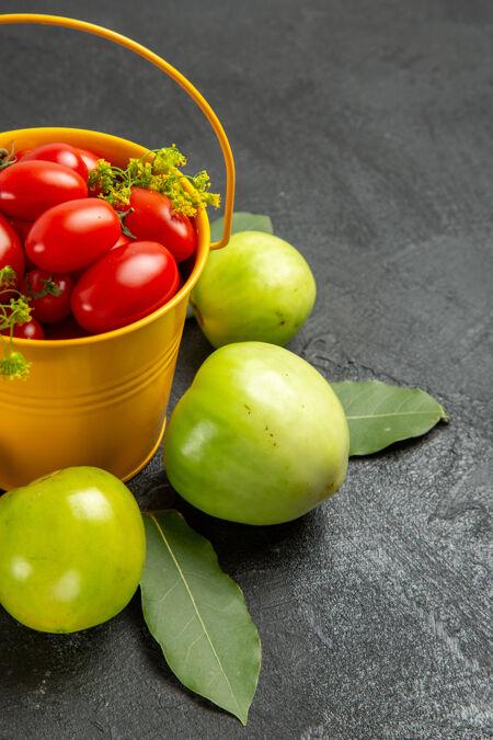 底部近距离观看黄色桶装满樱桃西红柿和莳萝花 绿色西红柿环绕在深色背景上