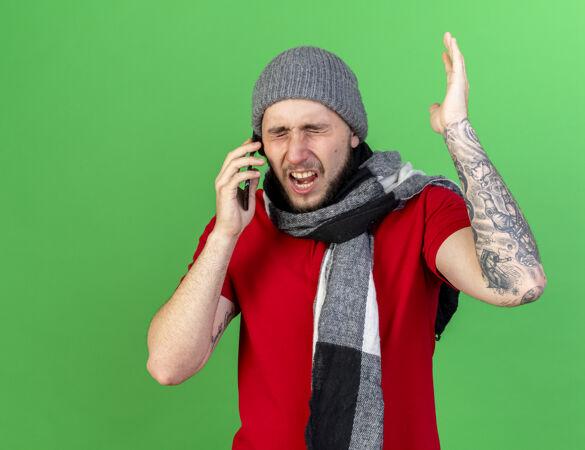 恼怒的年轻白种人 戴着冬天的帽子和围巾 站在那里举手打电话