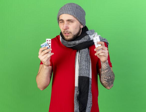 苍白的年轻白种人 戴着冬天的帽子 戴着围巾 手里拿着绿色的药片