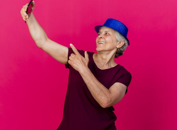 戴着派对帽的快乐的老太太看着粉色的手机