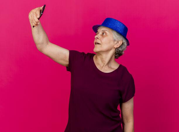 高兴的老妇人戴着聚会的帽子 拿着手机看着粉红色的