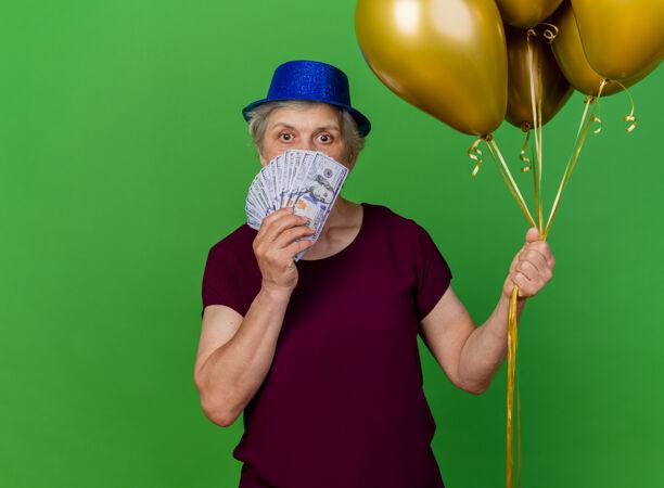 惊讶的老妇人戴着聚会的帽子 手里拿着钱和氦气球在果岭上