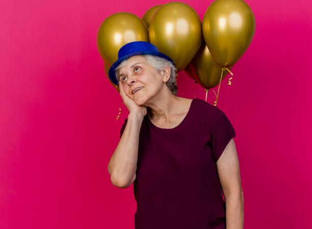 高兴的老妇人戴着聚会帽站在氦气球前把手放在粉红色的脸上