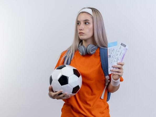 令人印象深刻的年轻白人运动女孩戴着耳机脖子上戴着背包头带