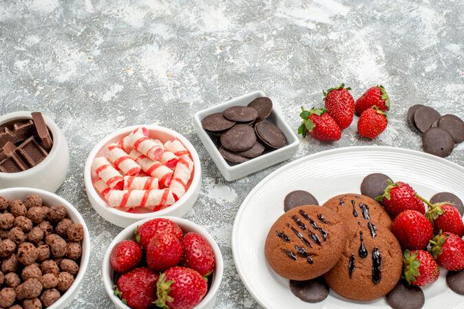 底部特写饼干草莓和圆形巧克力放在椭圆形的盘子里 糖果草莓巧克力麦片放在灰白色的桌子上