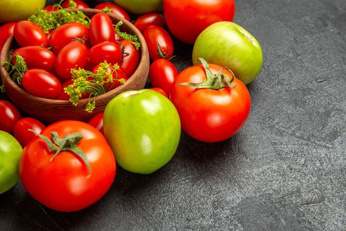 底部近距离观看樱桃红色和绿色的西红柿围绕着一个碗 深色背景上有樱桃西红柿和莳萝花