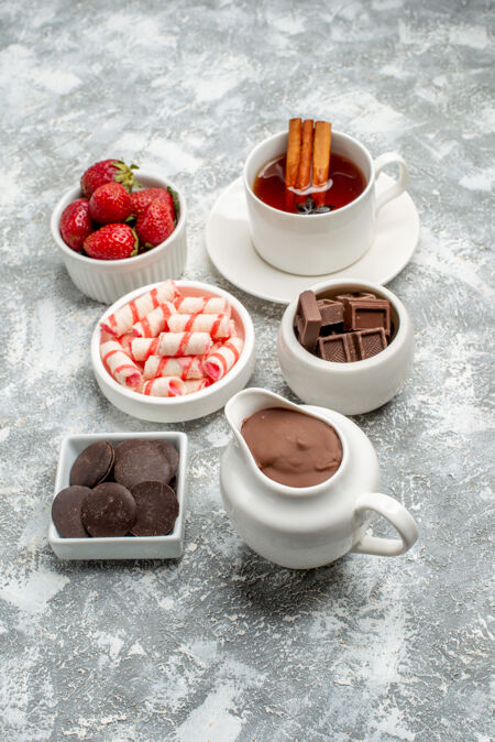 灰白色的桌子上放着可可糖果草莓巧克力茶肉桂和八角茴香籽的底视图碗