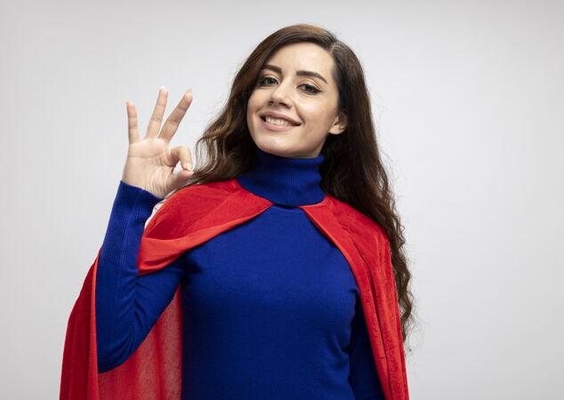 微笑的白人超级英雄女孩与红色斗篷手势确定手上的白色标志