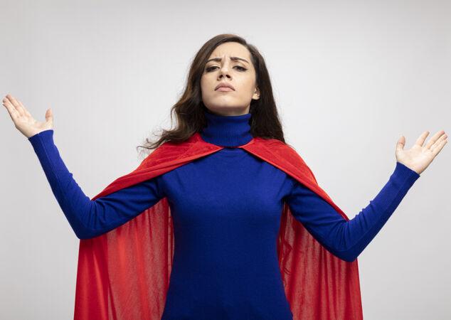 自信的白种人超级英雄女孩身穿红色斗篷 双手举在白色的胸前