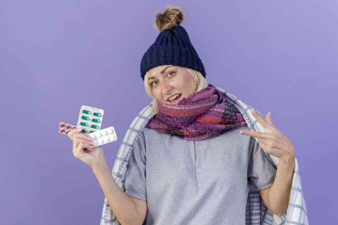 快乐的年轻金发病斯拉夫妇女戴冬季帽子和围巾